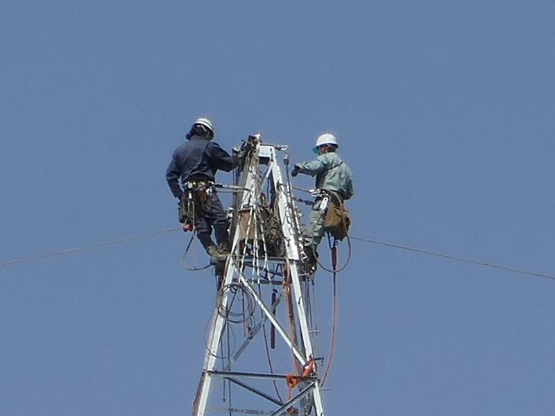 送電線の鉄塔の先端で作業中